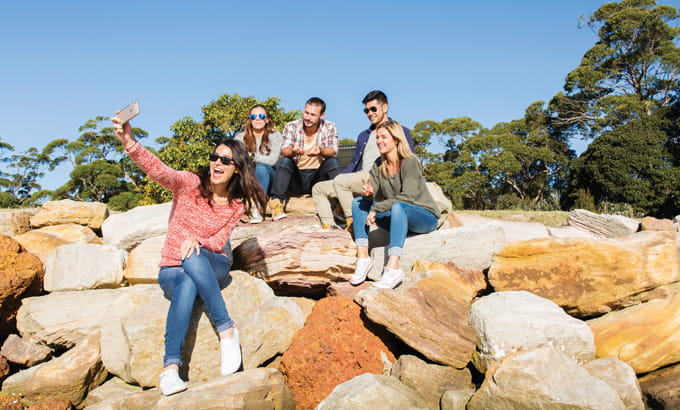 Young friends snap a photo at Bonnie Vale, Bundeena, Royal National Park. Photo: Simone Cottrell/OEH.
