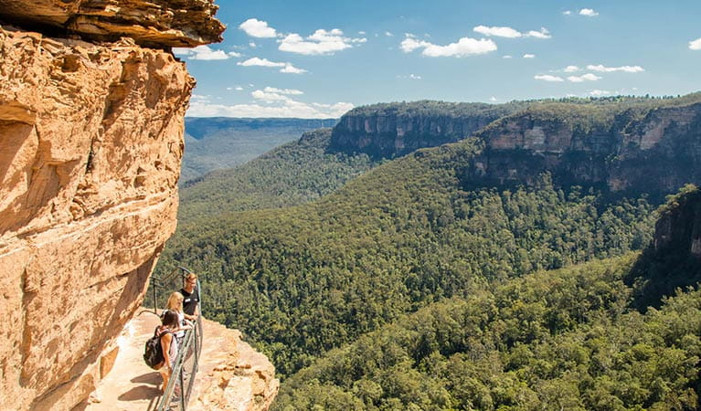 Three visitors enjoy views from National Pass at Wentworth Falls, Blue Mountains National Park. Photo: OEH