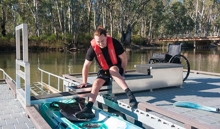 Man moving from stair platform into kayak at Edward River Bridge kayak launch. Photo: Rhys Leslie/OEH