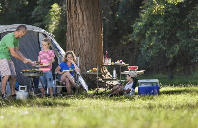 A family relaxes by their tent at Basin campground, Ku-ring-gai Chase National Park. Photo: David Finnegan/OEH
