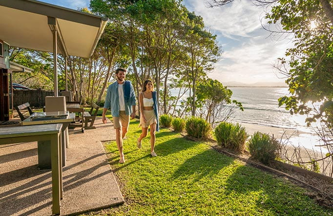 A man an woman walk on grass beside the verandah of Mildenhall Cottage, in Cape Byron State Conservation Area. Photo: John Spencer/DPIE