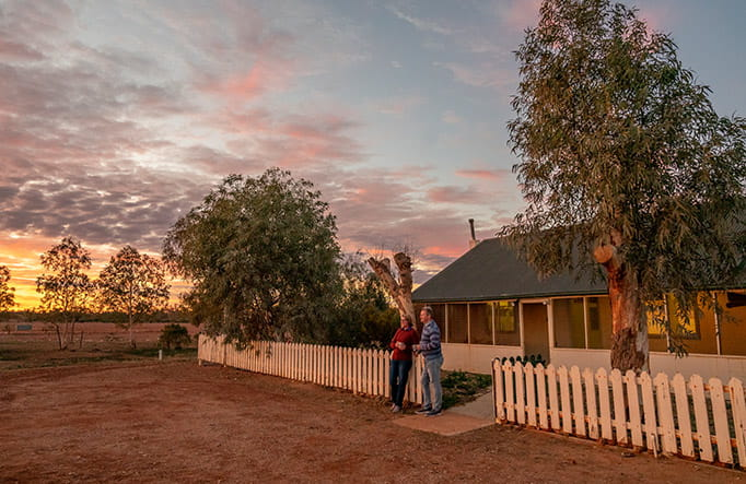 A couple watch the sunset outside Mount Wood Homestead, Sturt National Park. Photo: John Spencer/DPIE