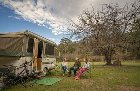 Three people sit on camp chairs beside a caravan at Wombeyan Caves campground. Photo: John Spencer/DPIE