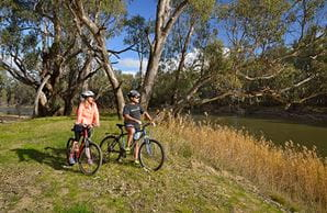 Two bike riders stop beside reed grass on the riverbank in Murrumbidgee Valley National Park. Photo: Gavin Hansford/DPIE