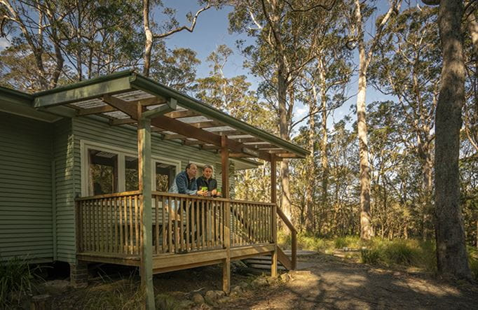 A couple stand on the balcony at Toms Cabin in New England National Park. Photo: John Spencer/OEH
