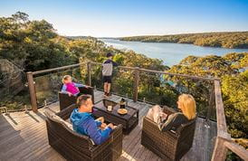 A family relax on the balcony of Hilltop Cottage, Royal National Park. Photo: J Spencer/OEH.