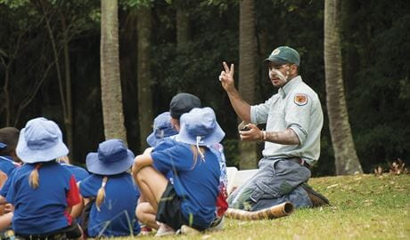 Students sitting on the grass, listening to an Arakwal Aboriginal guide on a school excursion to Cape Byron State Conservation Area. Photo: David Young/OEH