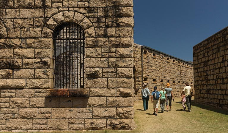 Image of a group touring the magnificent granite walls of Trial Bay Gaol