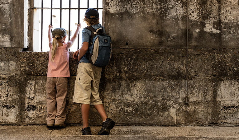 Image of kids peering through the bars in historic Trial Bay Gaol in Arakoon National Park.