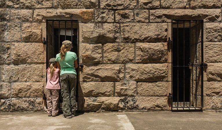 Image of children peering in the window of an old gaol cell at Trial Bay Gaol