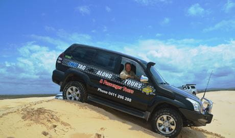 A man in a 4WD vehicle for Tag-Along and Passenger Tours travels down a dune under clear skies. Photo credit: Nicole Boyle © 4WD Tag-Along and Passenger Tours
