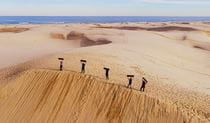 Aerial view of 5 people standing at the top of a massive sand dune, holding their sand boards in the air. Photo © 4WD Tours R Us