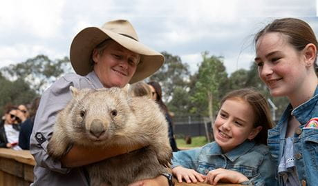 2 girls at Sydney Zoo with a zookeeper and wombat. Photo: © AAT Kings