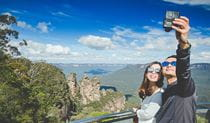 A couple take a selfie with the Three Sisters in the background on a tour with Activity Tours Australia in Blue Mountains National Park. Photo: Luke Thurlby © Activity Tours Australia