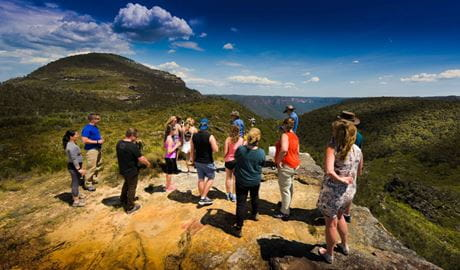 Tour guests gather at a rocky lookout platform with sweeping valley and mountain views. Photo © AEA Luxury Tours