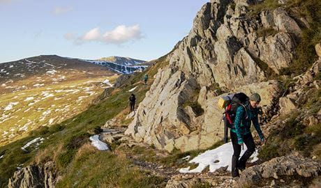 A group of hikers treks along a mountain path among rock crags, snow patches and open alpine heathland. Photo © Rachel Dimond