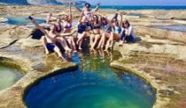 A group of friends cooling off at Figure Eight Pools, Royal National Park. Photo: Adam Hammond/Barefoot Downunder