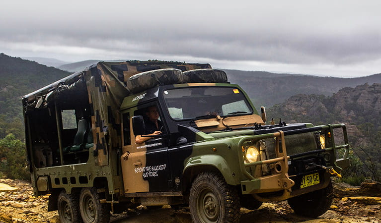 Open-back 4WD vehicle with camouflage paint on a rugged landscape overlooking valleys and mountains. Photo © Beyond the Blacktop 4WD Tours