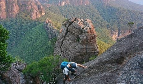 A man scaling a rock with the Budawangs wilderness in the background in Morton National Park.  Photo credit: Chris Zinon © Big Nature Adventures