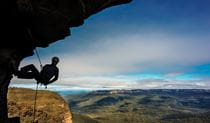 A silhouetted climber descends by rope beneath a cliff overhang, against a backdrop of sky and distant green valleys and mountains. Photo credit: David Hill © Blue Mountains Adventure Company