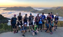 A group of runners stand on a lookout platform in front of a sweeping view of mountains and mist-filled valleys. Photo credit: Tony Williams © Blue Mountains Fitness