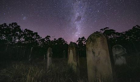 View of a dramatic and starry night sky  over an historic graveyard with tombstones, set in bushland. Photo credit: Pete Clifford © Blue Mountains Mystery Tours