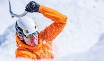 A man wearing an orange jacket and white helmet swings his ice axe in a snow-covered landscape. Photo © Martin Cankov