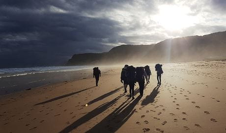 Bushwalkers with backpacks walk along a pristine beach at sunrise in the Royal National Park.  Photo credit: Mark Coulter © Collaroy Centre
