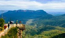 Members of a tour group stand on the rock shelf of a lookout with sweeping views of Blue Mountains National Park. Photo © Colourful Trips