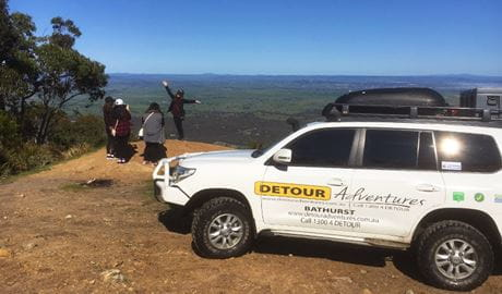 A Detour Adventures 4WD vehicle parked in front of a group of tour guests enjoying a panoramic view. Photo © Detour Adventures