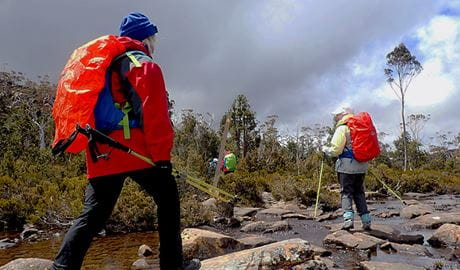 Women trek along a rocky river bed using hiking poles. Photo credit: Michele Michel © Diamonds in the Rough Adventures