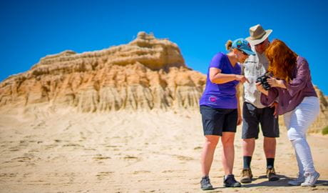 A group of 3 people gather near a Walls of China  rock formation in Mungo National Park. Photo credit: Robert Klarich © Discover Mildura