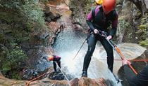 2 people in wetsuits descend on ropes past a waterfall into a steep canyon. Photo credit: James Waddell © Eagle Rock Adventures