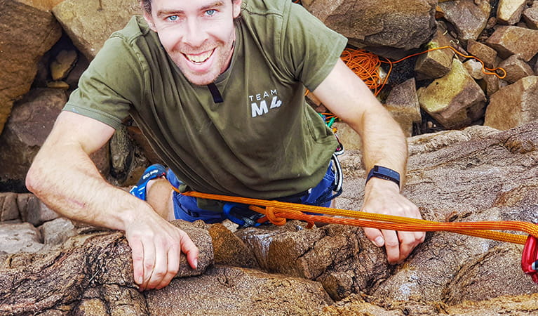 A young man smiles as he grips rock holds and climbs up a sheer cliff whilst roped in. Photo © Nash Hall