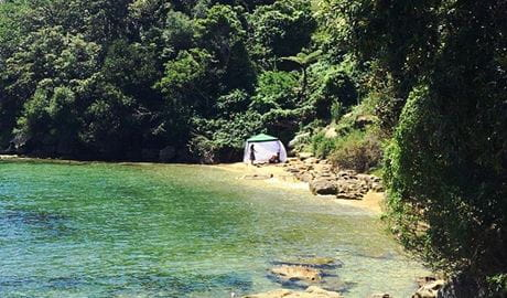 View of 2 people beneath a tent canopy at a secluded bay in Sydney Harbour. Photo © Exclusive East Tours