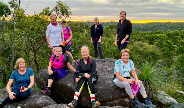 A group of women on a Fittrek training session gather at twilight next to a rocky outcrop with wide views over park landscape. Photo ©  Roz Warne