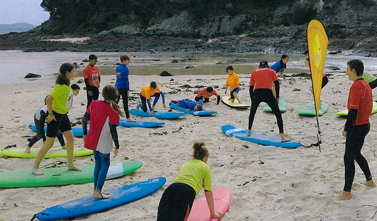 A group of surfers with boards practice stance alongside their instructor at a beach. Image © Gary Hughes Surface School of Surf