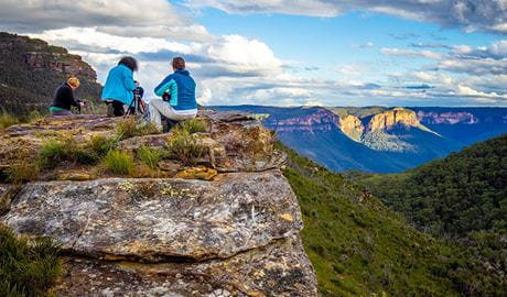 3 people with camera equipment on a rock ledge overlooking a steep valley with sweeping mountains views. Photo © Gary P Hayes Photography