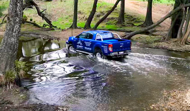 A blue 4WD vehicle makes a river crossing in bushland. Photo © Getabout 4WD Adventures