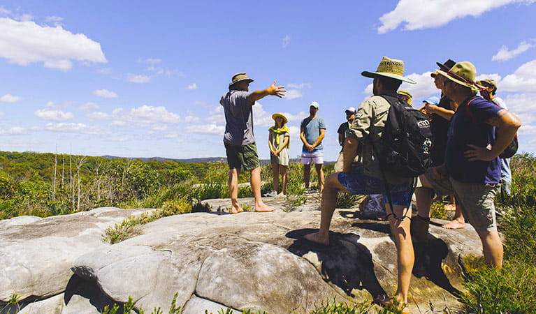 A Girra Girra guide standing on a weathered rock platform shares his knowledge with a group of tour guests. Photo © Girri Girra Aboriginal Experiences