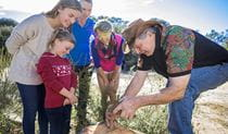 Guringai Tours' Laurie Bimson with a family group of tour guests on an Aboriginal cultural tour.  Photo © Guringai Tours