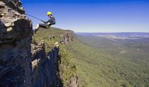 A man abseils down cliff face in the Blue Mountains against a backdrop of valleys and hills. Photo © Neil Aldred