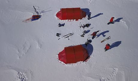 Aerial view of a group of people standing near 2 red tents in a winter snow camp. Photo © Eric Philips