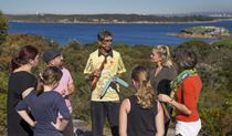 Tour group watching demonstration by Tim Ella at La Perouse in Kamay Botany National Park. Photo: Dallas Kilponen