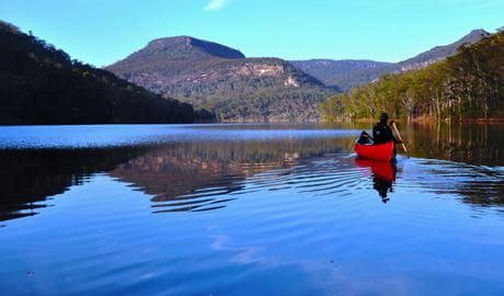 A lone person in a kayak paddles across calm lake waters. Photo credit: Glyn Stones  © Kangaroo Valley Safaris
