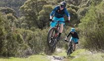 Two mountain-bikers charge up a hill in Kosciuszko National Park. Photo: Adam McGrath