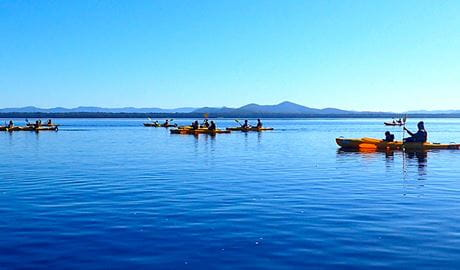 Tour group with people in double kayaks on calm waters in Myall Lakes National Park. Photo © Lazy Paddles