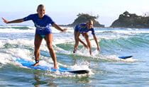 A pair of women in Le'ts Go Surfing rash shirts smile as they ride a small wave near Byron Bay. Photo © Let's Go Surfing