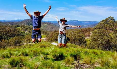 A man and woman leap into the air near a walking track, with cliffs and valleys of the Blue Mountains in the background. Photo © Life's An Adventure.