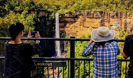 Women photograph a waterfall cascading down a cliff face.  Photo: Steve Nomchong © Local Travel Planner